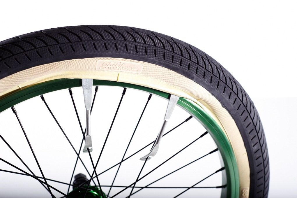 Push the tyre into the middle of the rim. If you can't remove the tyre with your hands, get a pair of tyre levers and hook it under the beading of the tyre, avoiding nipping the tube against the metal. Work them carefully around the rim.